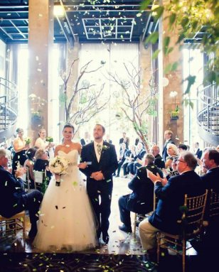 Officially hitched! Staff lined the upstairs balcony and surprised guests by fluttering down an array of green, ivory and black confetti strips.