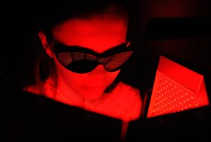 """Photograph of a young woman receiving red light therapy and wearing protective goggles, from """"The Health Benefits of Red Light Therapy: Legit or Hype?"""""""