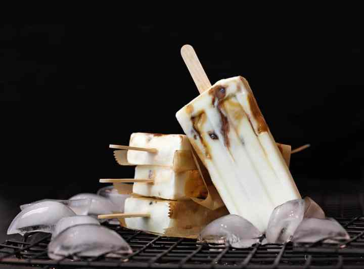 Caramel cream popsicles with date caramel and nutella ripples on ice with a black background.