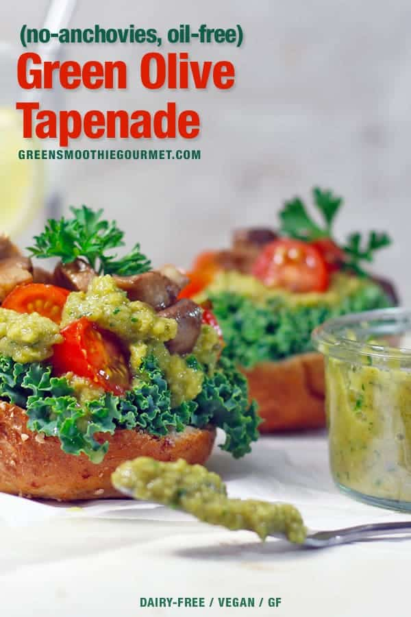 a sandwich stuffed with tomatoes, mushrooms, kale, and spilling over with green olive tapenade which is also on a spoon to the right.