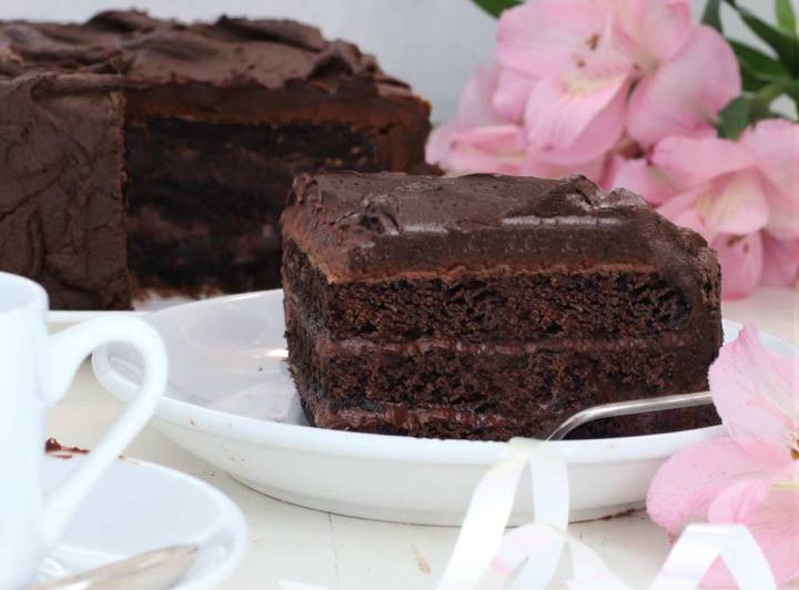 A slice of chocolate cake on a white table with the whole cake behind it and a pink flower behind it.