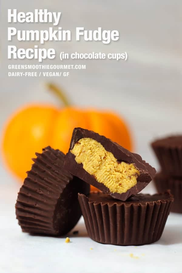 Three chocolate cups filled with pumpkin fudge and with a pumpkin in the background.