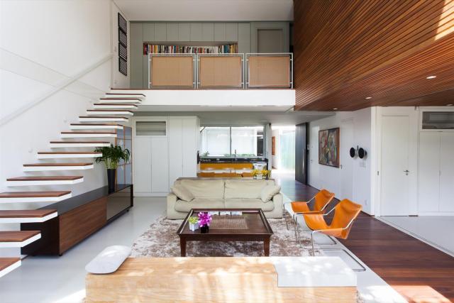 Detalhe para o piso monolítico, cortado pelo deck, que marca o eixo longitudinal da residência. (Fonte: Galeria de Arquitetura).