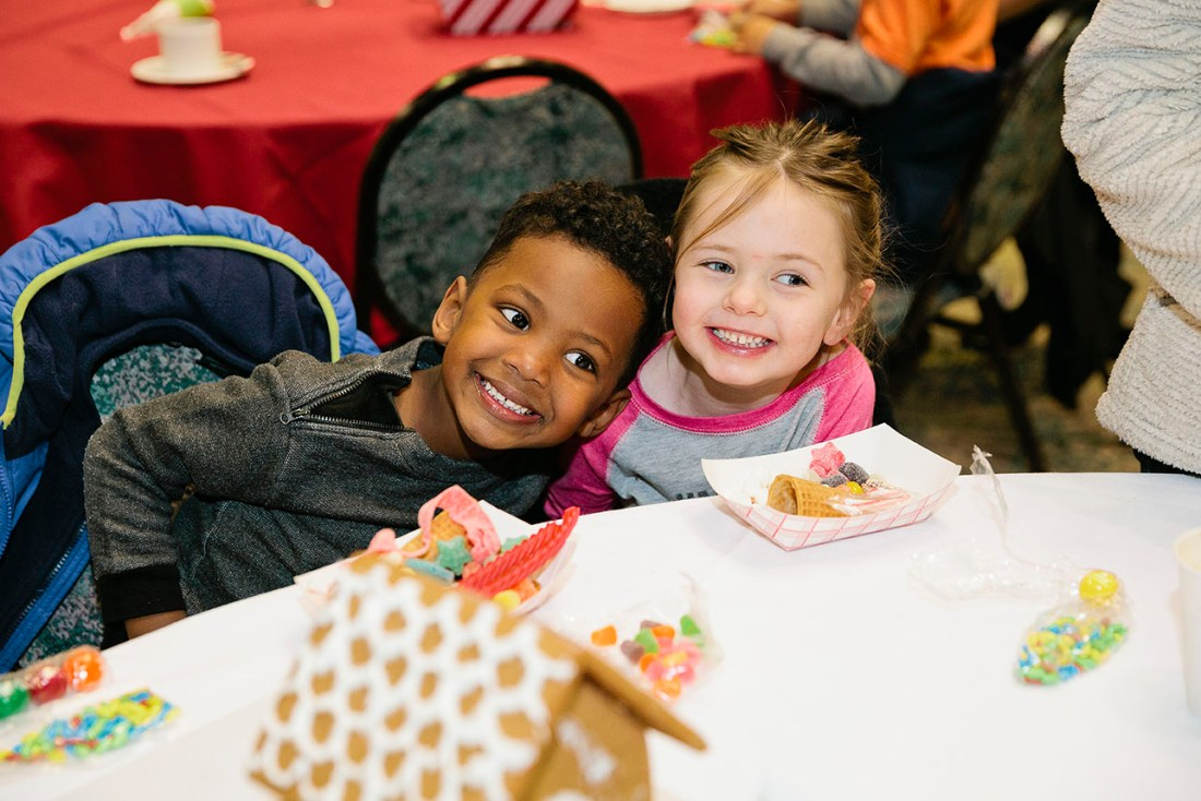 children smiling with gingerbread house