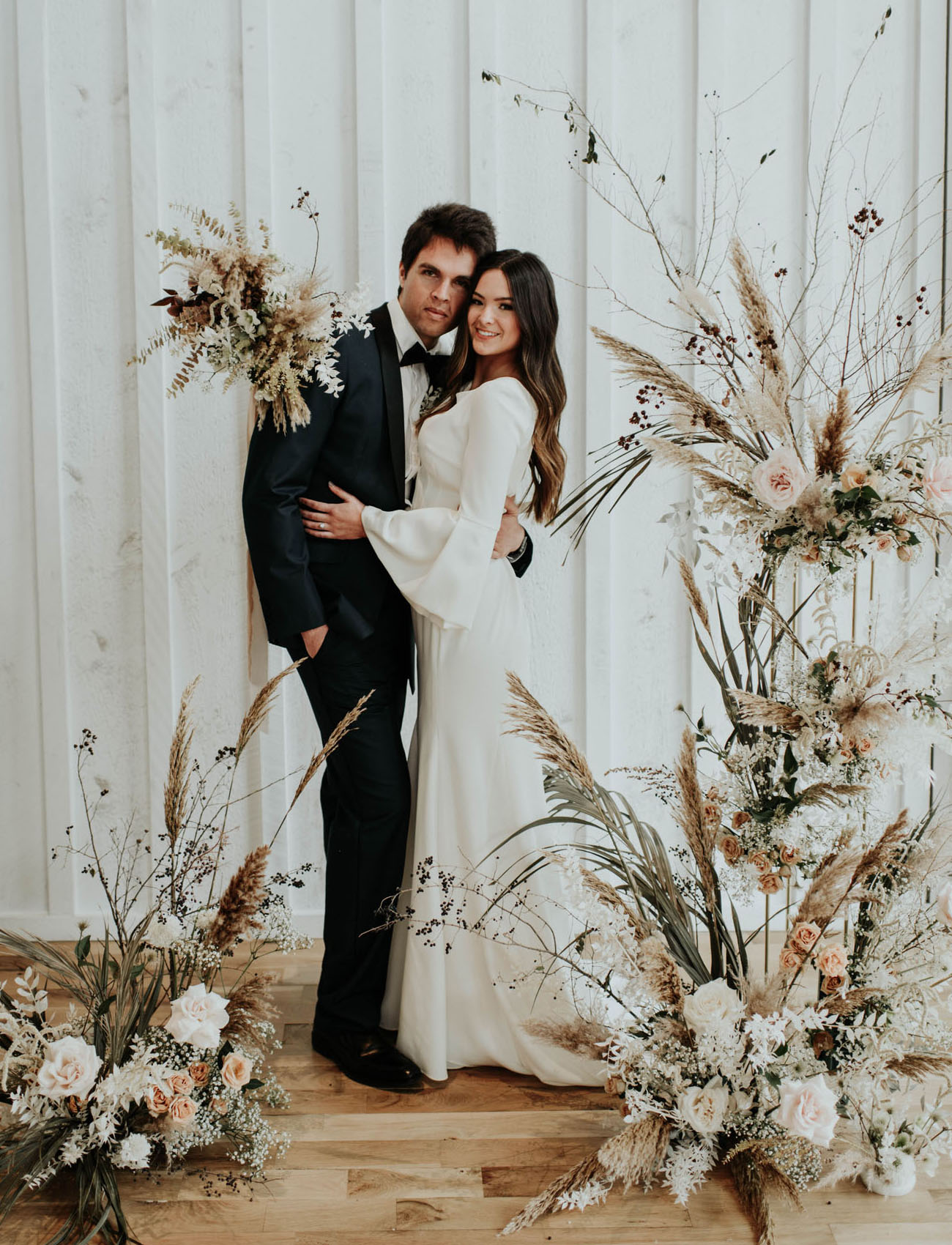 Wedding couple at modern boho wedding ceremony with dried flowers