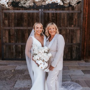 bride standing with mother of the bride wearing a neutral tone pant suit