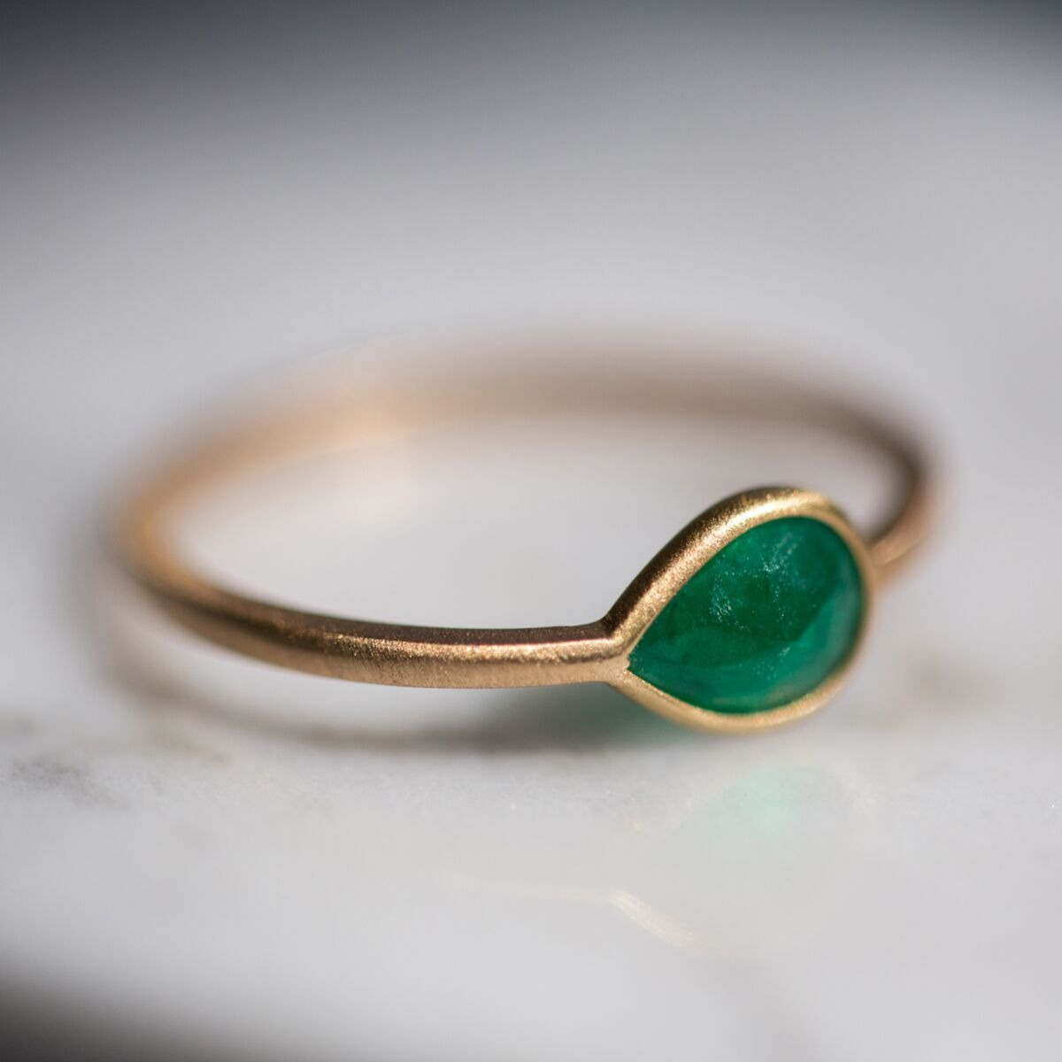 18K gold tilted pear shaped emerald ring