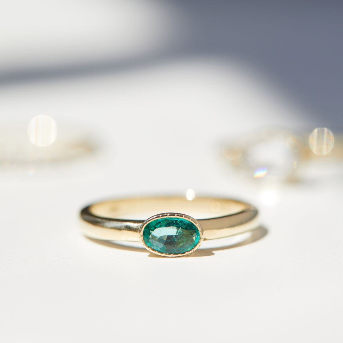 milgrain detail solitaire emerald engagement ring with gold band
