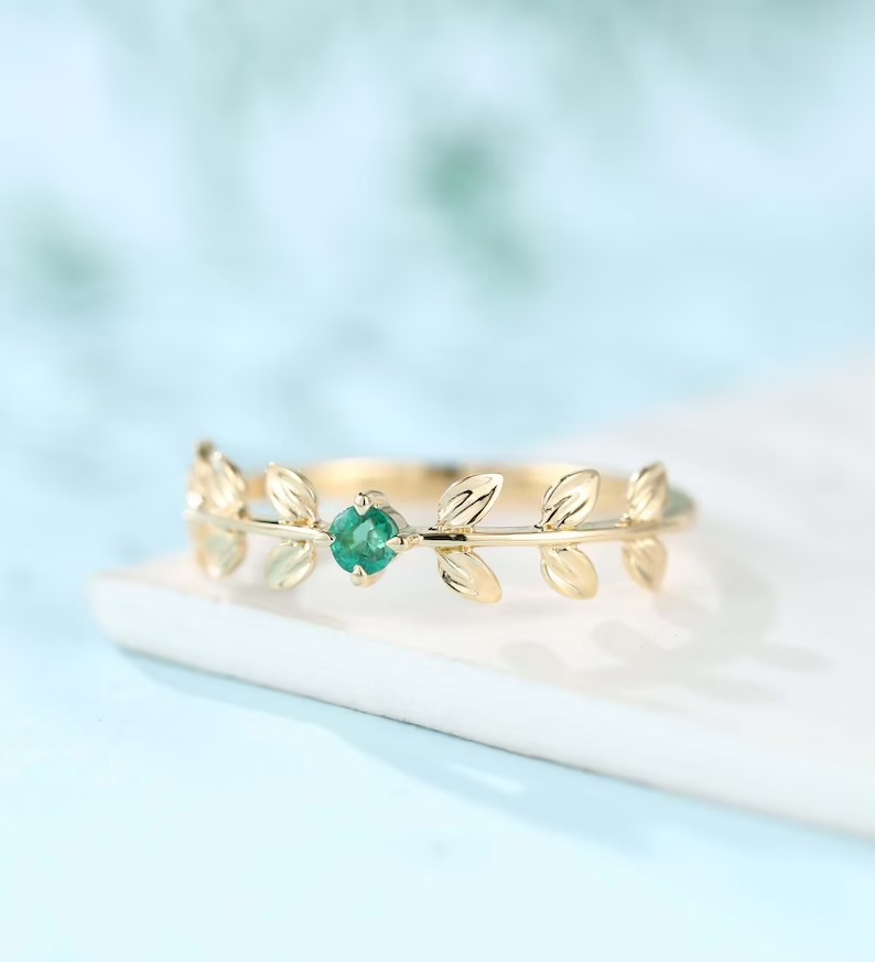 solitaire emerald engagement ring with gold leaf design on the band