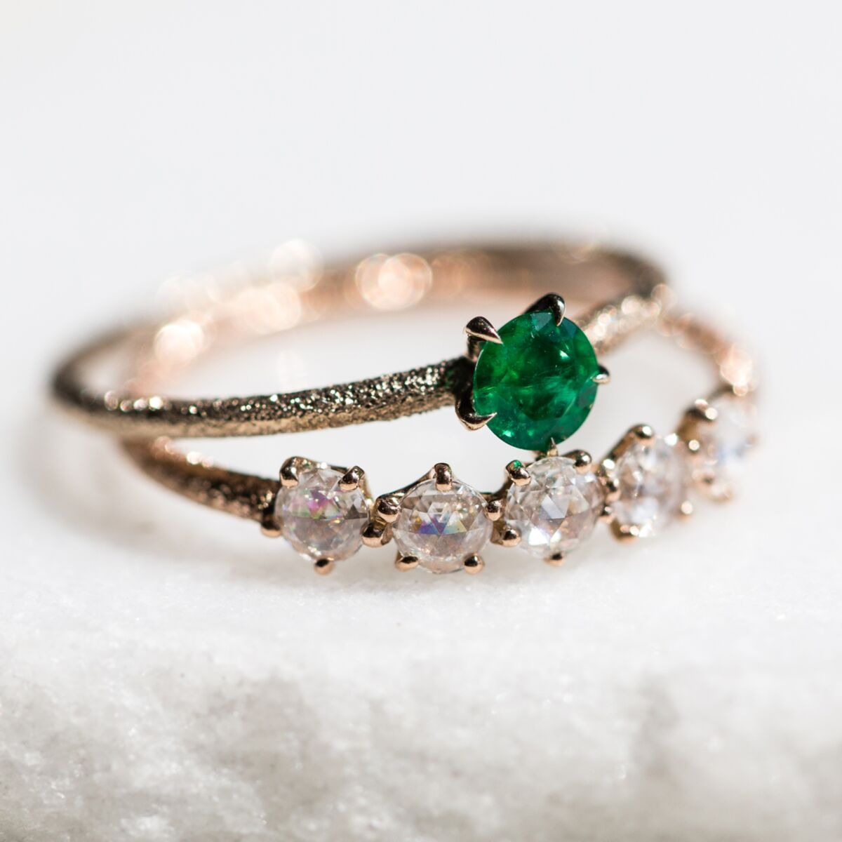 solitaire emerald engagement ring with textured 18K gold band