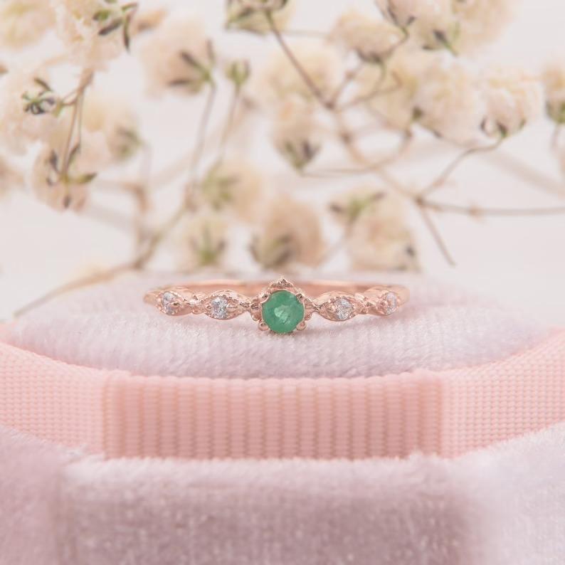 vintage rose gold emerald ring sitting in a blush pink ring box