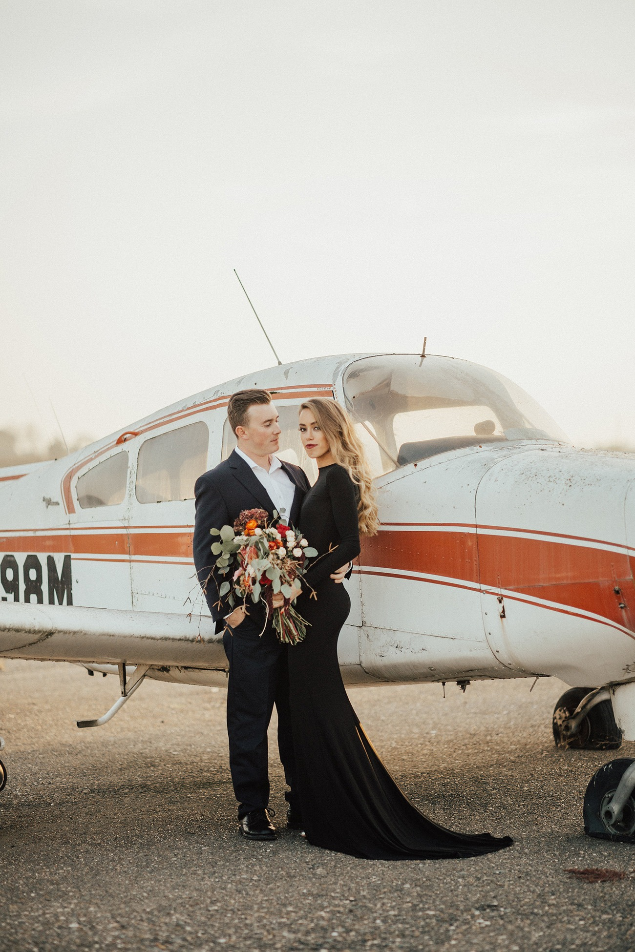 bride standing in front of an airplane in a black mermaid wedding dress with long sleeves