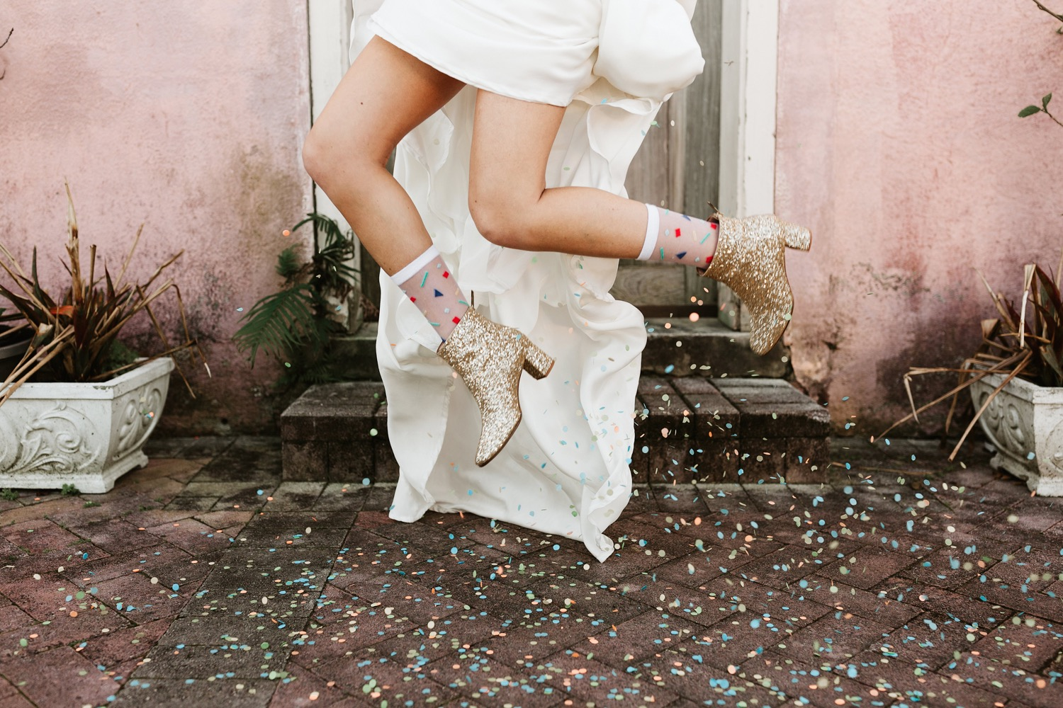 bride wearing gold wedding boots