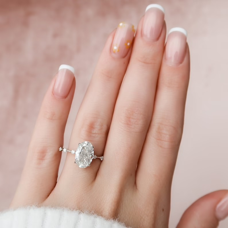 minimalist oval moissanite engagement ring with unique stone detailing on the band