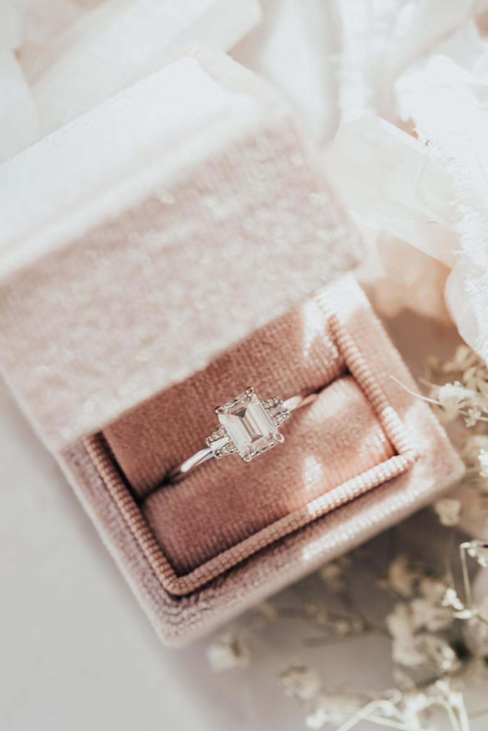 moissanite vs diamond emerald cut ring in blush pink velvet box