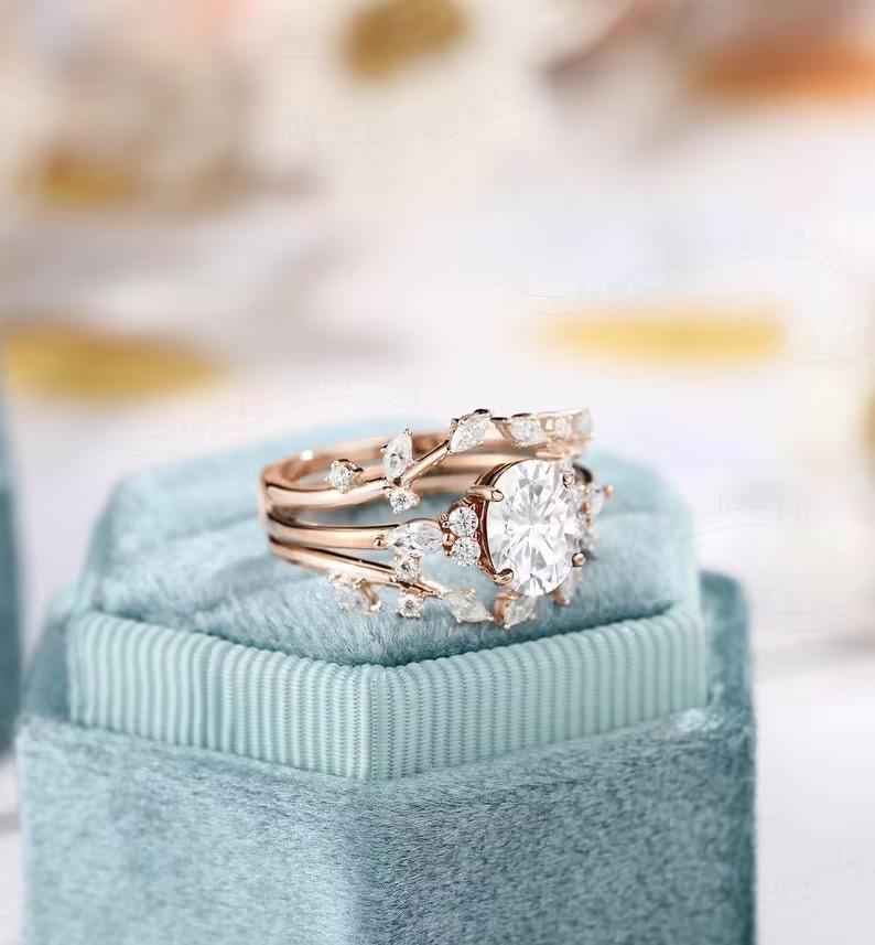 moissanite vs diamond gold leaf ring set sitting in a light blue velvet box