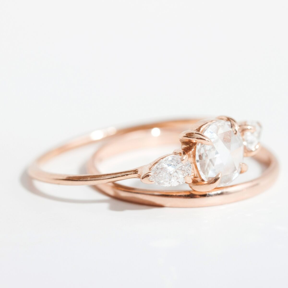 three stone unique rose gold engagement ring with a simple band and romantic look