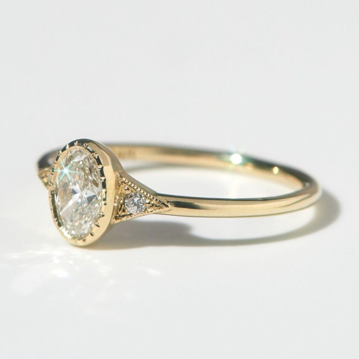 oval diamond bezel set gold band engagement ring
