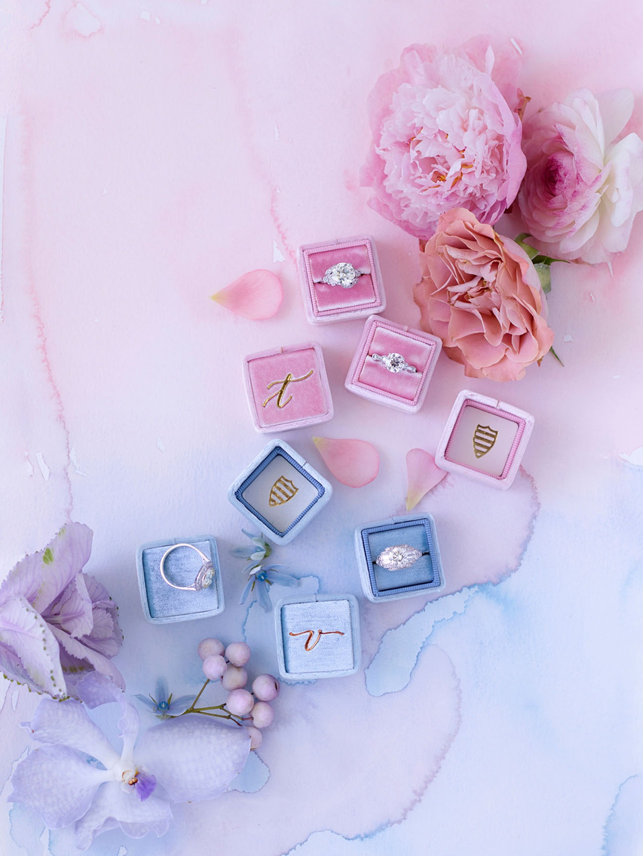 unique engagement rings sitting in velvet Mrs Boxes on a watercolor backdrop adorned with pink and purple flowers