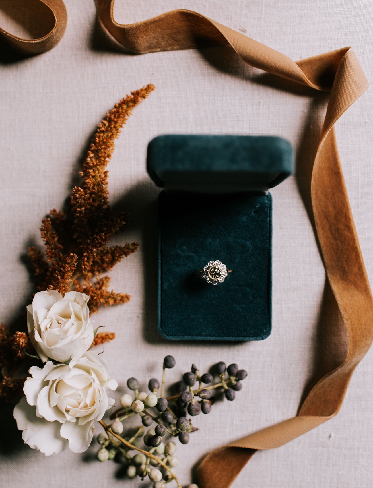 floral inspired diamond engagement ring sitting in a dark green velvet box