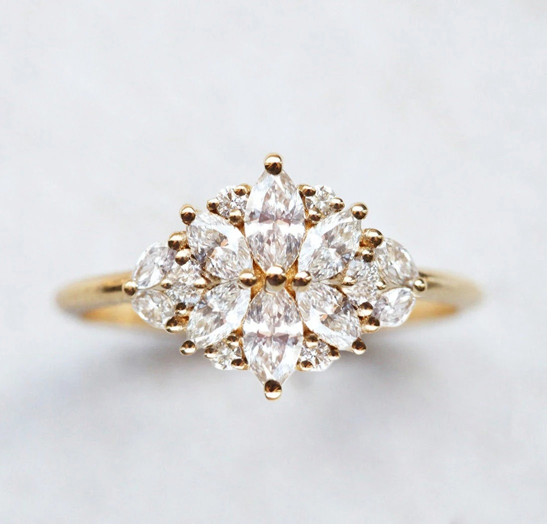 unique marquise engagement ring with gold band and multiple diamond clusters