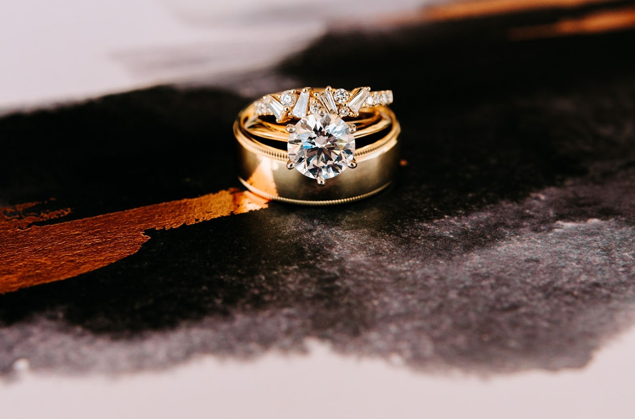 modern engagement ring stacked in between two gold wedding bands
