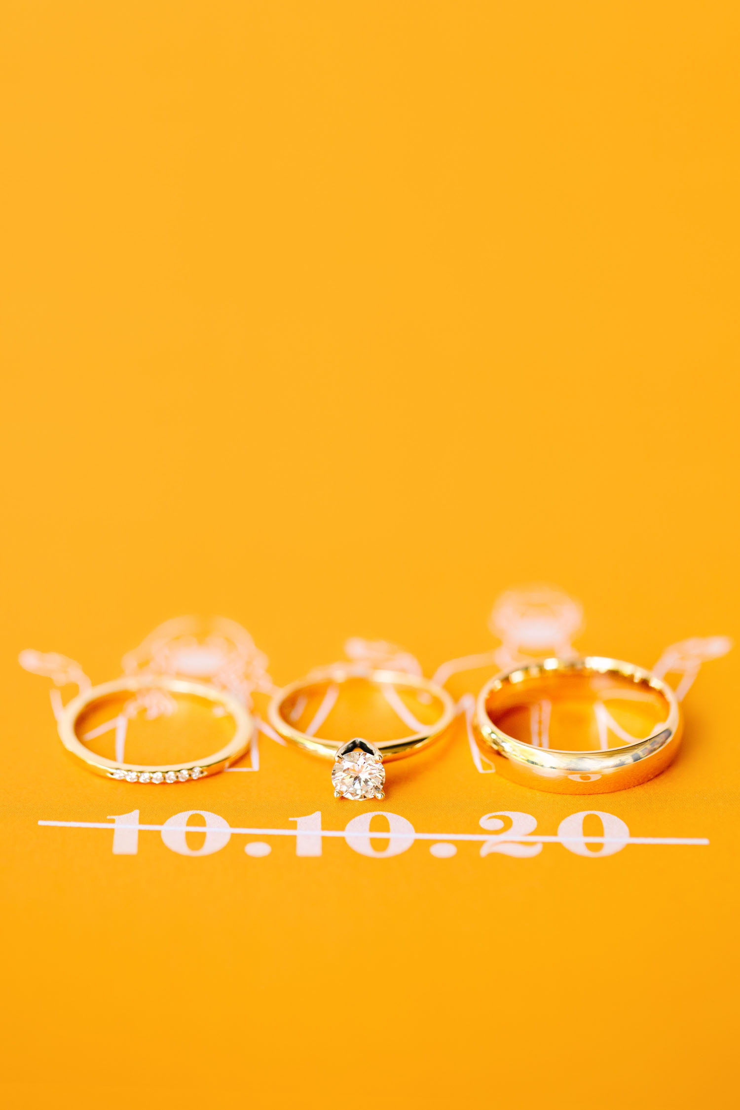 solitaire engagement ring sitting on a colorful yellow wedding invitation