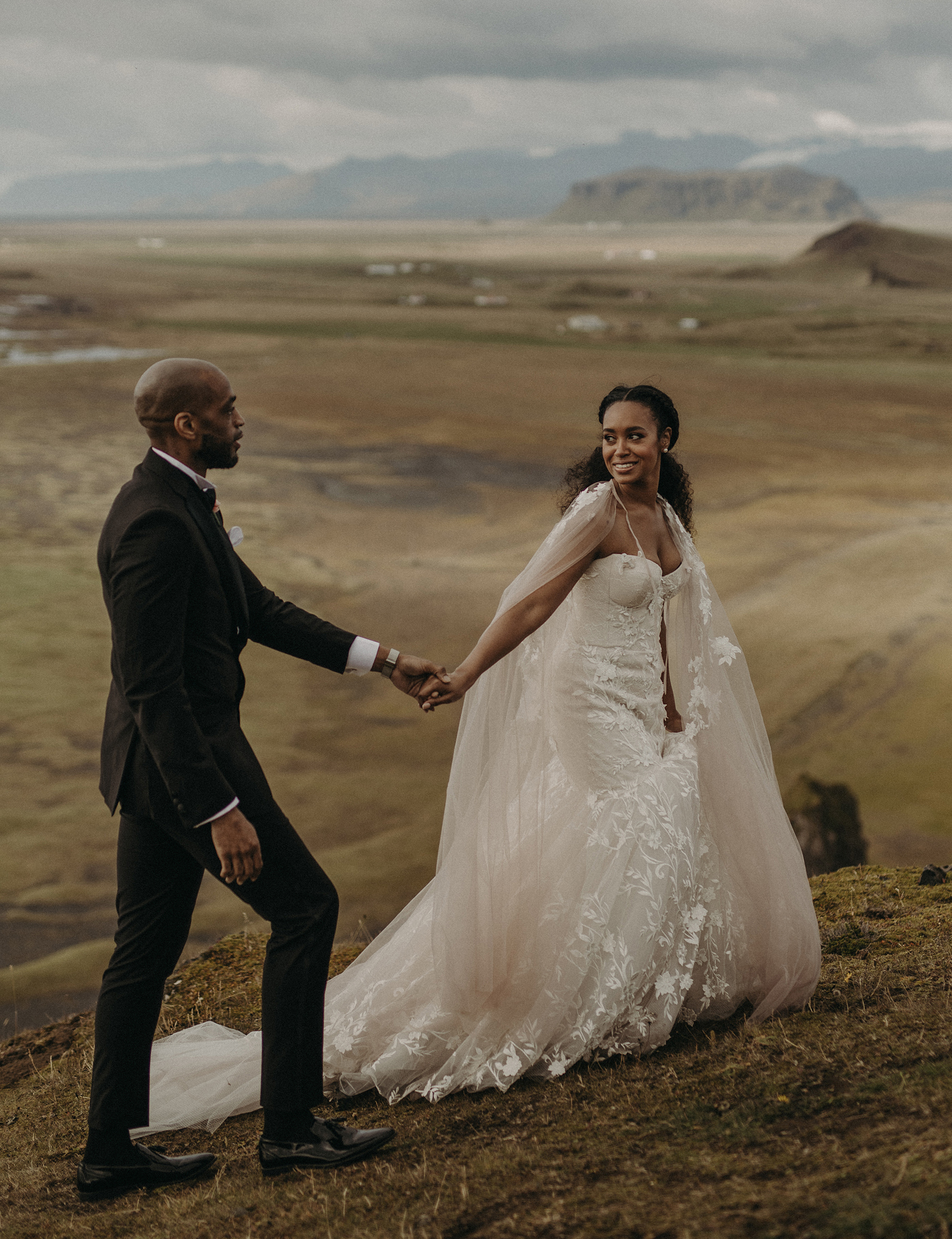 bride and groom walking up a mountain in a bridal cape