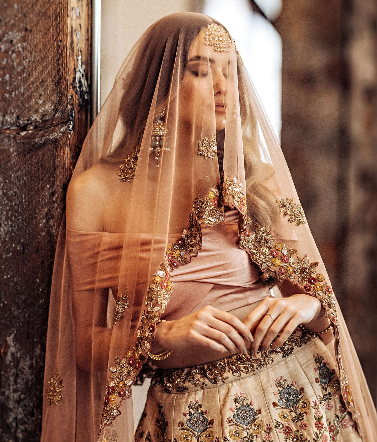 bride wearing blush tone traditional Indian wedding attire and jewelry