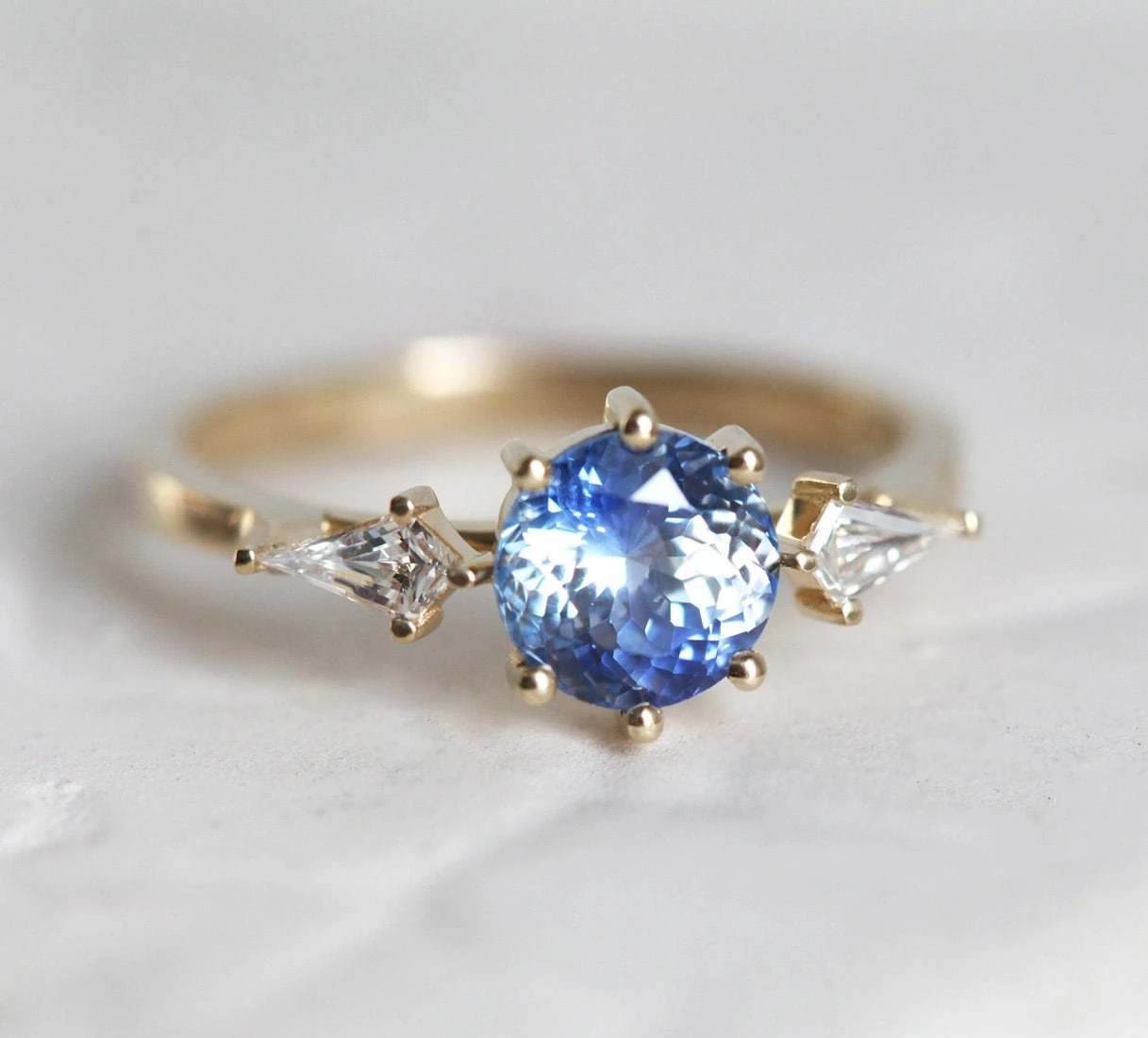 circular blue sapphire engagement ring with kite shaped diamonds on either side of the center stone