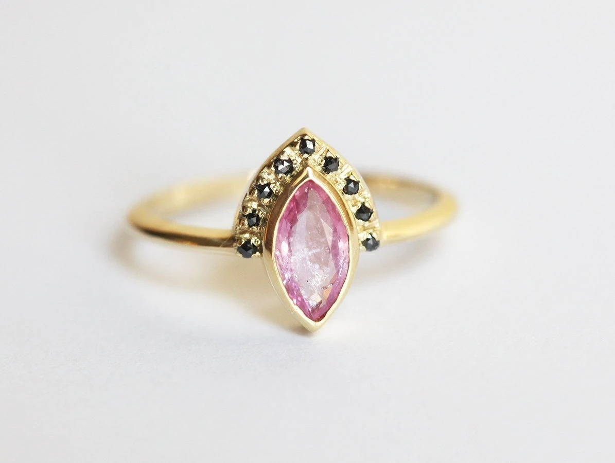 marquise pink sapphire ring with black diamond accented crown and gold band