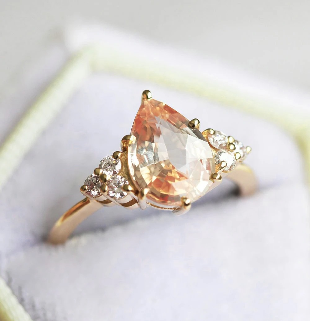 pear shaped peach sapphire engagement ring with diamond trio on either side of the center stone