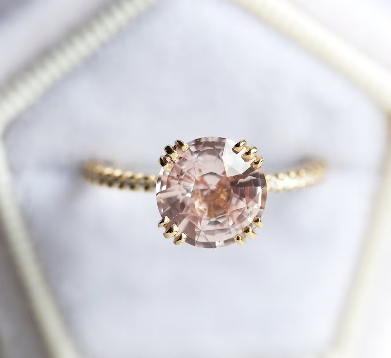 intricate round solitaire sapphire engagement ring in a champagne peach color