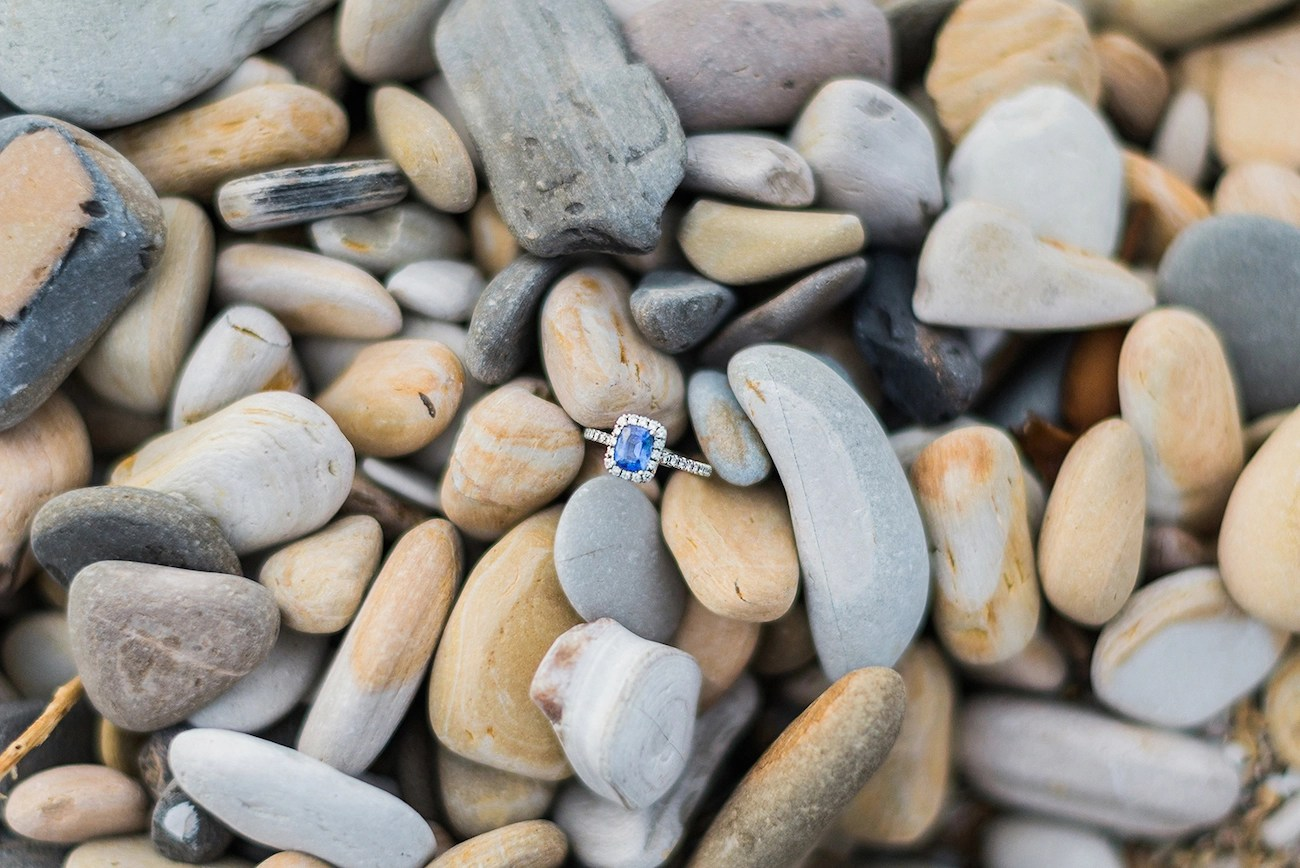 cushion cut blue sapphire engagement ring with a diamond halo sitting in a bed of pebbles