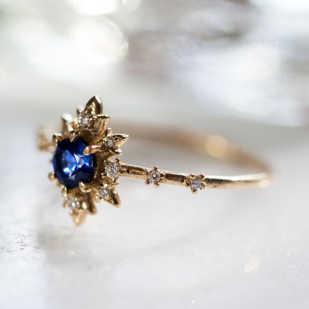 sun inspired blue sapphire engagement rings with yellow band and diamond accents