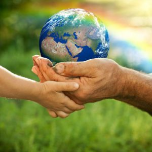 a childs hand and a mans hand holding a globe