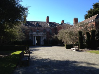View of the front of the house, with formal clipped hedges.
