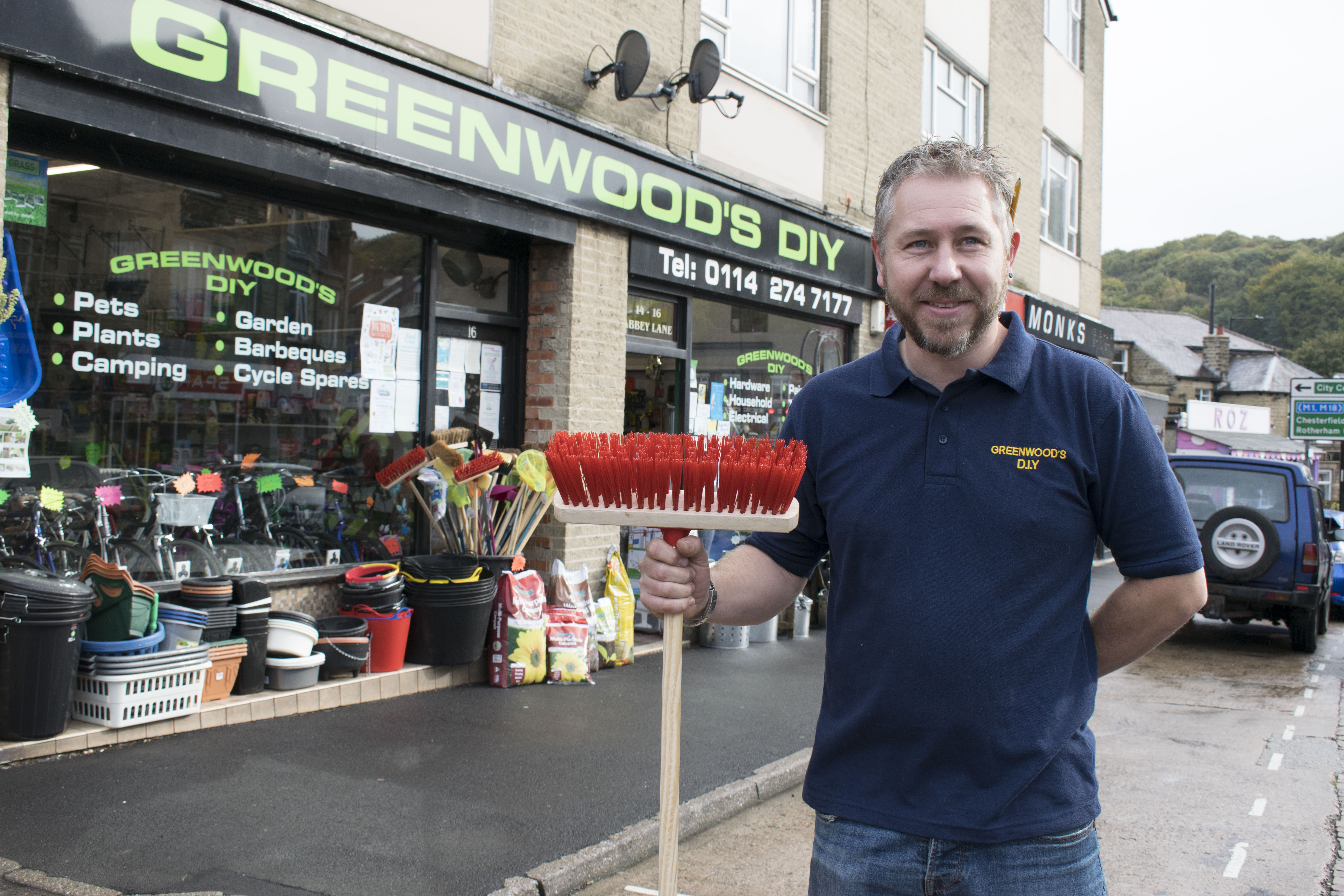Nic with his broom outside the shop