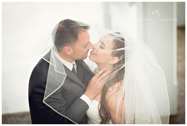 Kissing under the veil at their wedding at Bay Pointe Inn