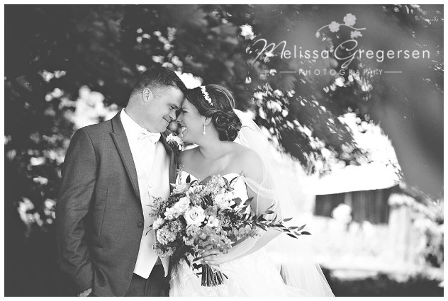 Black and white photograph of scrunchy nose smiles with bride and groom