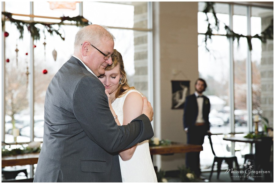 Father daughter dance at wedding with groom watching in the distance.