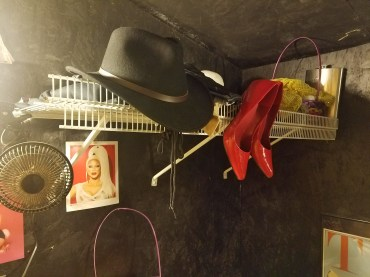 Cowboy hat and patent-leather pumps in the dressing room.