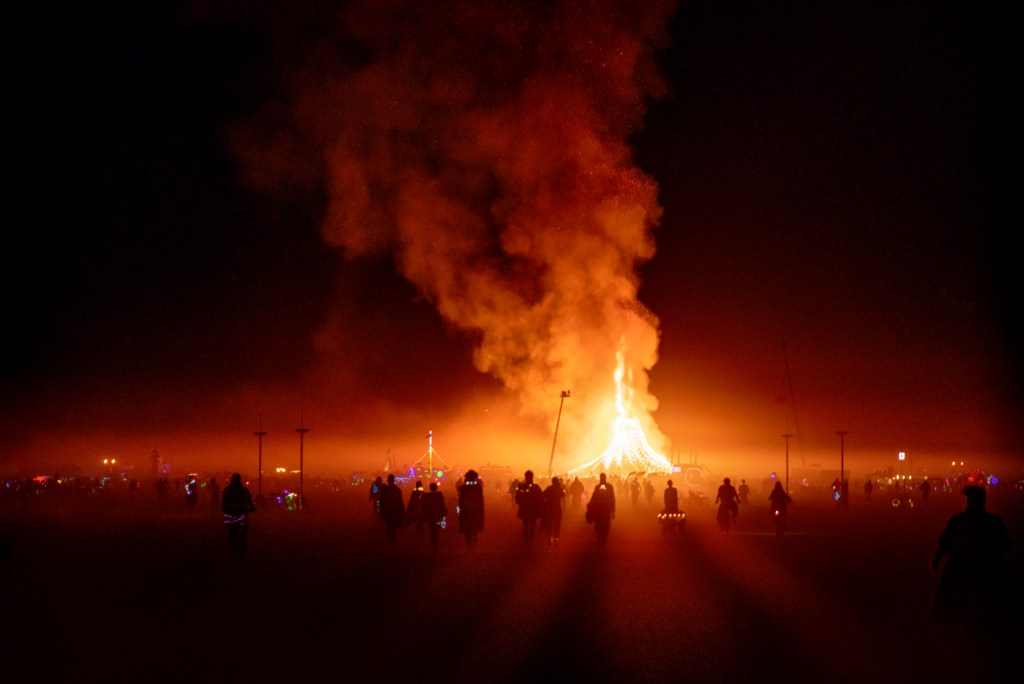 People in a small dust storm walking towards the Temple Burn at Burning Man
