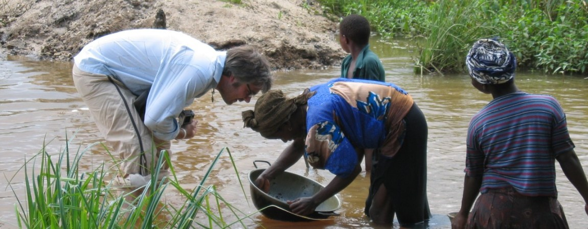 Woman gold panning in a diamond washing pit, Sierra Leone 2005.