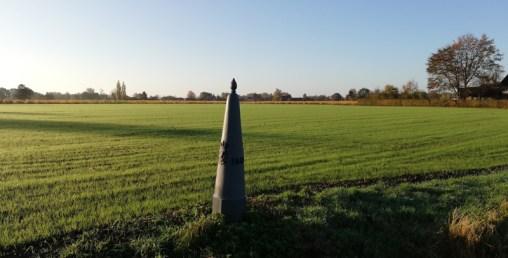Grenspaal in het gras bij Budel-Schoot