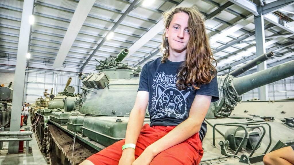 Teenage boy with gorgeous long hair sitting on top of a tank, while visiting the Tank Museum in Dorset