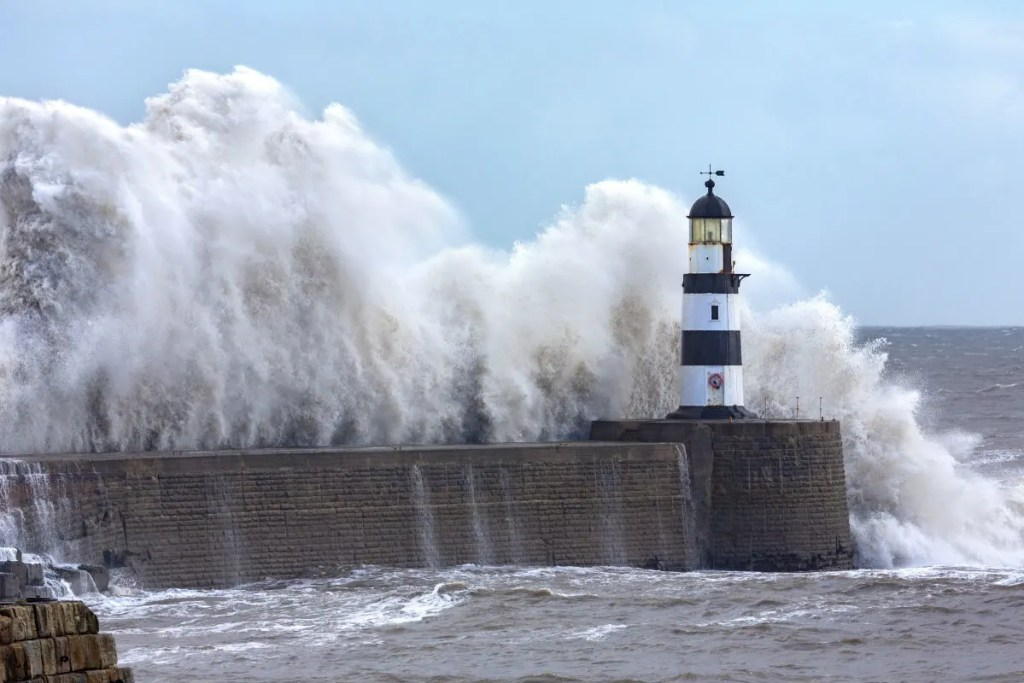 The iconic black and white Seaham Lighthouse, standing at the end of the North breakwater, with huge waves crashing over to top of it