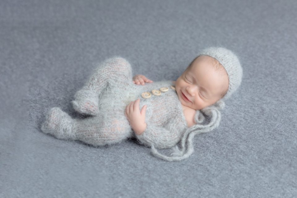 baby smiling in a grey outfit during his photo session, moms favourite photo