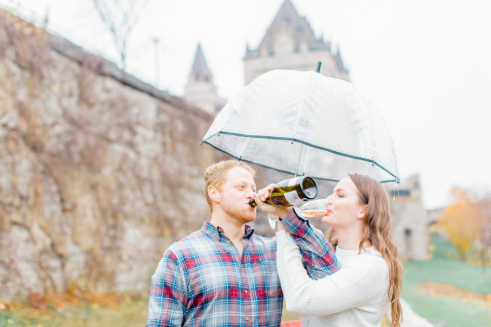 fall Engagement Session Downtown Ottawa during Sunset National Art Gallery grey loft studio ottawa wedding photographer videographer engagement kanata orleans nepean beautiful locations for engagement photos in ottawa chateau laurier majors hill park pop champagne pink and black dress rainy day engagement session using clear umbrella