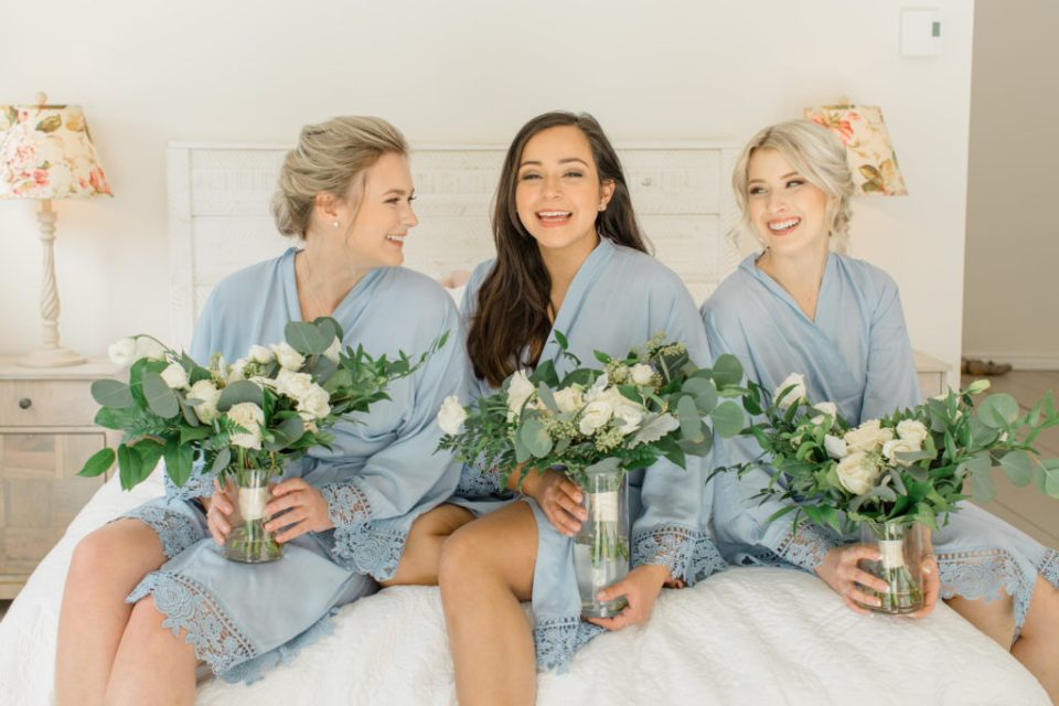 bridesmaids in blue robes - holding bouquets in water - sitting on a bed - quebec wedding photographer Wakefield bridgeottawa wedding photographer couple getting married in winter le belvedere wedding sunset grey loft studio couples in love affordable kanata photographer cheap wedding fun wedding romantic wedding bridesmaids